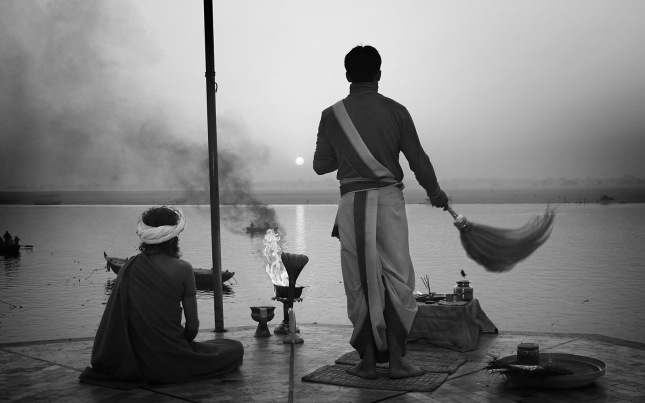 Priest saluting the sun in the Ganges